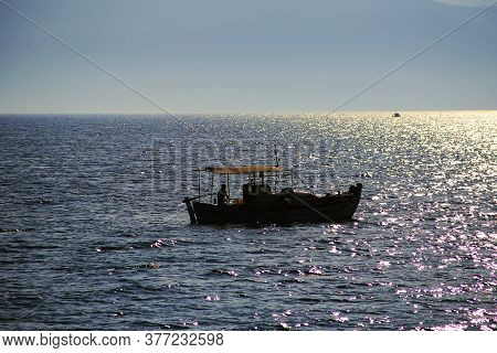 A Fishing Boat On The Glistening Open Sea. In The Distance The Mountains Of The Island. Sunset.