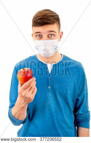 Young Man In A Flu Mask Hold An Apple Isolated On The White Background