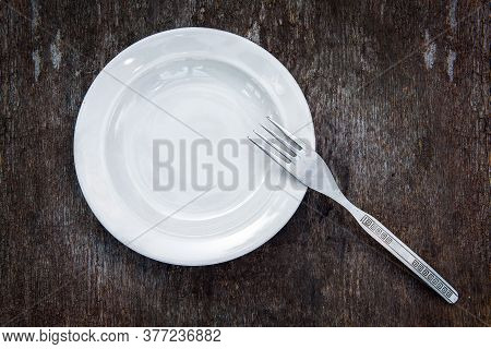 Empty Plate With A Fork On The Grunge Wooden Board Background