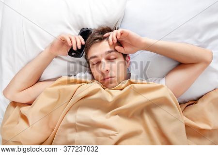 Tired Young Man Sleep In The Bed With A Mobile Phone