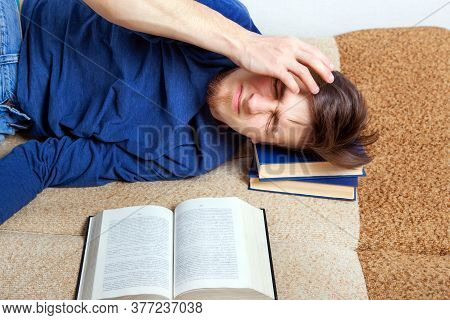Sleepy And Tired Young Man On The Sofa With A Book
