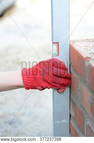 A Building Contractor Or A Mason Is Using A Spirit Level For Keeping Brickwork Upright And Level, Ch