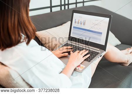 Young Woman Working On Laptop Computer While Sitting At The Living Room. Work From Home Concept