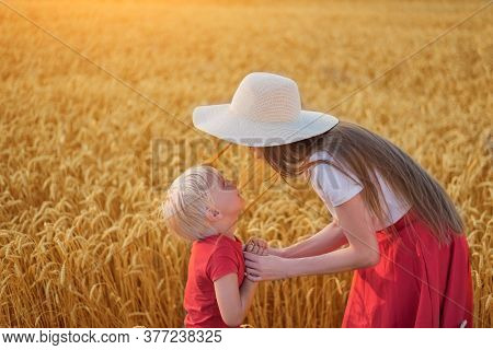Brother And Sister Walking Through Wheat Field. Siblings Play On Field.