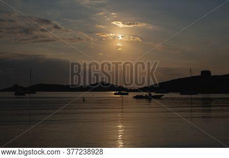 Sunset Over Sea Water. Boats Anchored At Vourkari Port, Kea Island, Greece.