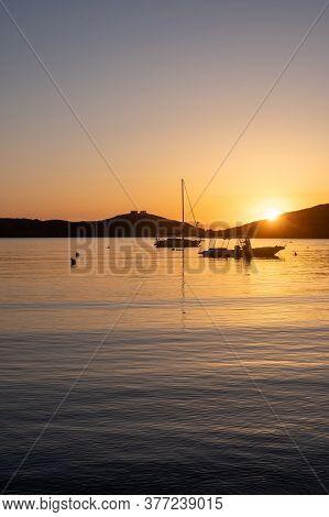 Sunset Orange Color Over Sea Water. Boats Anchored At Vourkari Port, Kea Island, Greece.