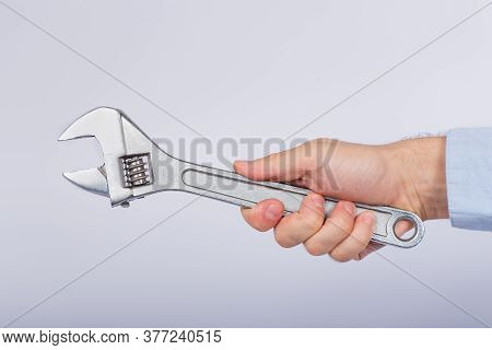 Male Hand Holding Wrench On A White Background. Mechanical Key In Hand. Side View.