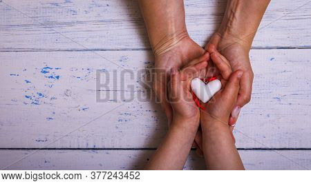 Mother's Day Celebration With Parent Woman Holds Young Kid's Hands Supporting Heart, Donation For Nu