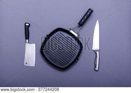 Empty Grill Pan On Home Kitchen Table. Metal Knives On A Grey Background, Grill Pan And Blade. Flat