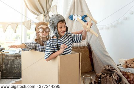 Little boy and little girl in pilot hats playing pilots sitting in paper box at home