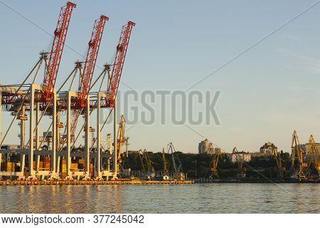 Three Portal Cranes In The Evening Port