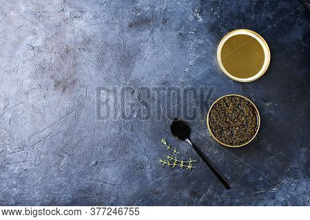 Black Sturgeon Caviar With A Black Spoon And A Dark Background. Seafood, Healthy Food.