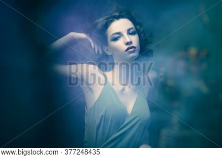 Magnificent brunette young woman posing in a room with light haze. Beauty, fashion. Romance and mystery.