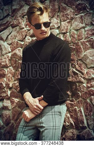 Art portrait. Handsome young man model posing in black pullover, jeans and sunglasses next to stone wall. Men's style, beauty. Fashion shot.