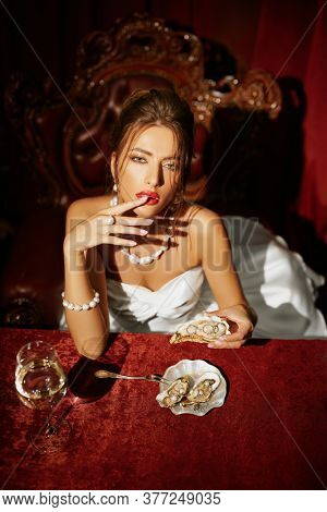 Gorgeous bride woman dines in a luxury restaurant with oysters and precious jewelry with pearls and gold. Jewelry and luxury lifestyle. Wedding fashion.