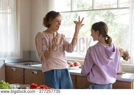 Overjoyed Mother And Teenage Daughter Having Fun In Modern Kitchen