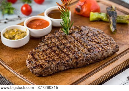 Fresh Delicious Juicy Steak With Vegetables On Wooden Background.