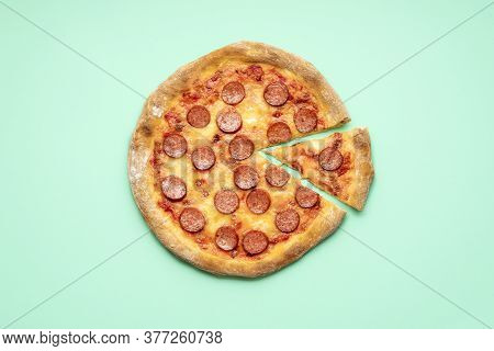 Flat Lay With A Pepperoni Pizza On A Green Mint Background. Single Slice Of Pizza Pepperoni Top View