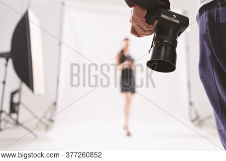 Selective Focus Of Photographer Holding Camera In A Photoshoot With Blurry Model At The Background,