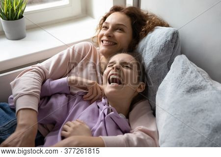 Overjoyed Mother And Laughing Teenage Daughter Relaxing On Bed Together