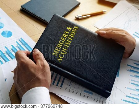 Businessman Holds Book About Mergers And Acquisitions Ma.