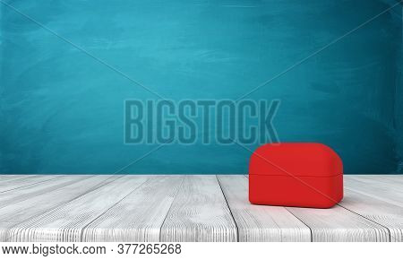 3d Rendering Of Closed Red Ring Box On Wooden Table Near Blue Wall.