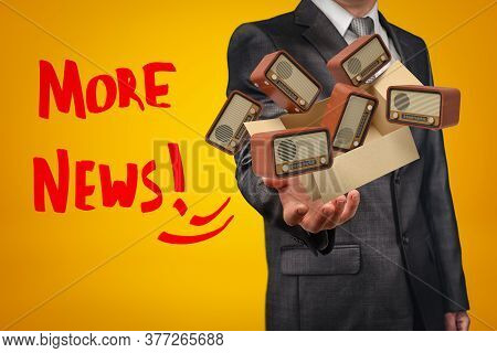 Businessman Holding Cardboard Box Filled With Retro Radio Sets And More News Sign On Yellow Backgrou