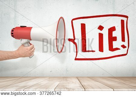 Mans Hand Holding Red And White Megaphone Against Grungy White Wall With Big Speech Bubble That Says