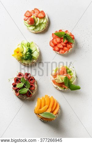 Puffed Rice Cakes With Different Toppings Friuts And Vegetables On White Background, Flat Lay. Vegan