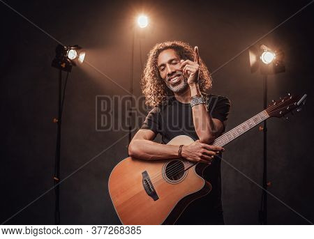 Middle Aged Hispanic Man Musician In Black T-shirt Holds Guitar. View Of Musician In The Spotlight