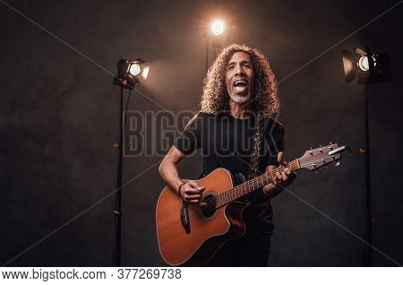 Middle Aged Hispanic Musician In Black T-shirt Emotionally Singing And Playing Guitar. View Of Music
