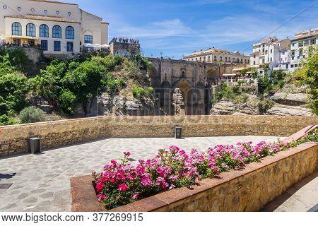 Flowers In Front Of The Historic Puente Nuevo Bridge In Ronda, Spain