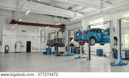 Two Lifted Cars At Service Station Prepared For Diagnostics And Repair Indoors. Car Service, Repair,
