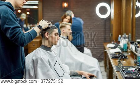 Working Process In Barbershop. Side View Of A Young Handsome Guy Getting Trendy Haircut By Professio