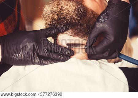 Close-up Side View Of Young Bearded Man Getting Beard Haircut By Hairdresser At Barbershop. Getting