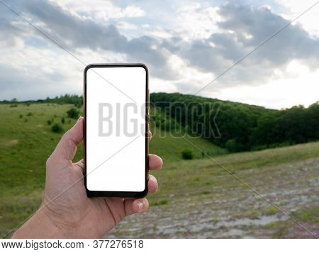 Hand holding smart phone with blurred backgroung. Blank screen for montage. Mockup image.