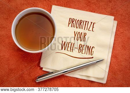 prioritize your well-being inspiraitonal note - handwriting on a napkin with a cup of tea, healthcare, healthy lifestyle and personal development concept