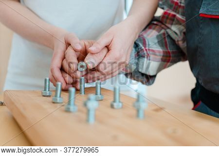 Closeup on hand of man in occupational therapy screwing nut on bolt