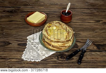 National Russian Cuisine. A Many Of Fresh, Hot, Baked Pancakes With Butter On A Green Plate And Jam