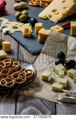 Maasdamer Cheese And Camembert Cheese. Cheese Dish With Olives, Herbs, Snacks On An Old Black Wooden