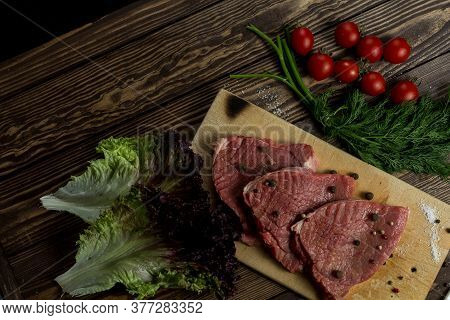 Raw Meat Beef Slices On A Wooden Chopping Board With Fresh Organic Vegetables, Onion, Garlic, Spices