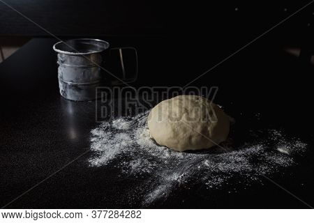 Pizza Dough Sprinkled With Wheat Flour Lies On A Black Table. Sieve In The Background. Cook At Home.