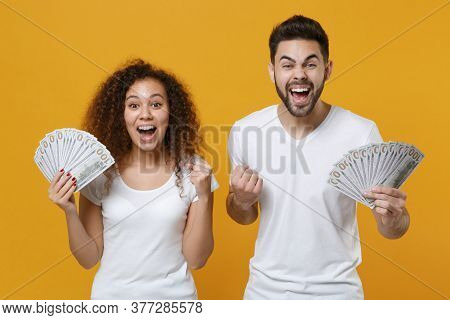 Excited Couple Friends European Guy African American Girl In White T-shirts Isolated On Yellow Backg