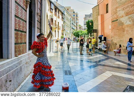Malaga, Spain - September 03, 2015: Street Performer Dressed Up In Spanish Traditional Wear Holding