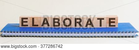 Elaborate Word On Wooden Cube On Blu Background