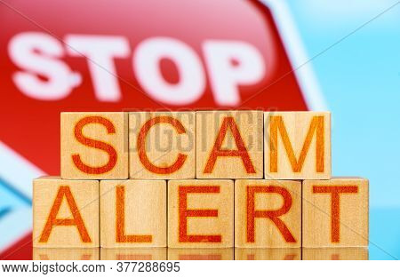 Scam Alert. Wooden Blocks With Scam Alert Lettering And Stop Sign On Background