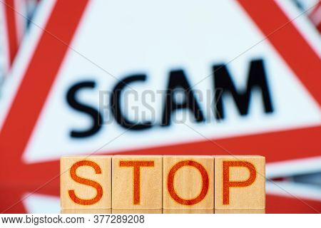Stop Scam. Wooden Blocks With Stop Inscription And Scam Sign On Background