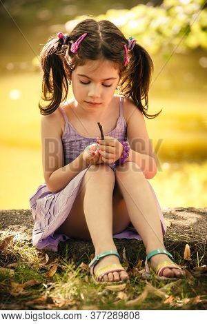 Outdoor vibrant candid portrait of adorable small daughter with ponytails.