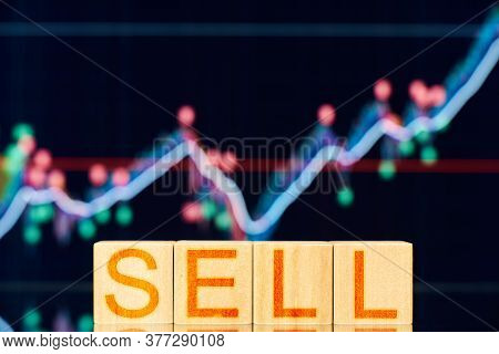 Sell. Wooden Blocks With The Inscription Sell On The Background Of The Stock Chart