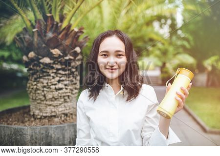 Happy Young Asian Female Woman In A Park With Reusable Plastic Bottle, Smiling. Outdoor Recreation U